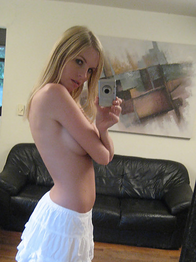 Cute blond teen takes pictures of herself in the mirror